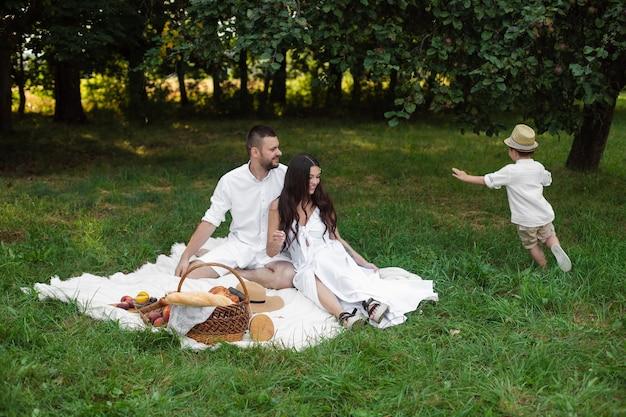 Obraz wesołej kaukaskiej mamy, taty i ich dziecka bawiących się razem i uśmiechających się w ogrodzie