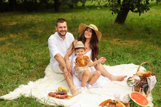 Obraz wesołej młodej kaukaskiej kobiety i mężczyzny trzyma dziecko na rękach, uśmiecha się i raduje