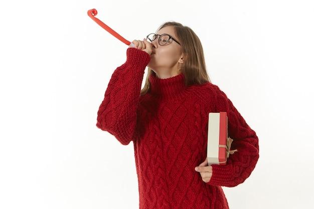 Obraz wesołej, pięknej młodej kobiety w świątecznym nastroju świętującej nowy rok lub boże narodzenie, noszącej ciepły sweter z dzianiny i okulary, trzymającej pudełko i dmuchającej papierowy róg, dobrze się bawiąc