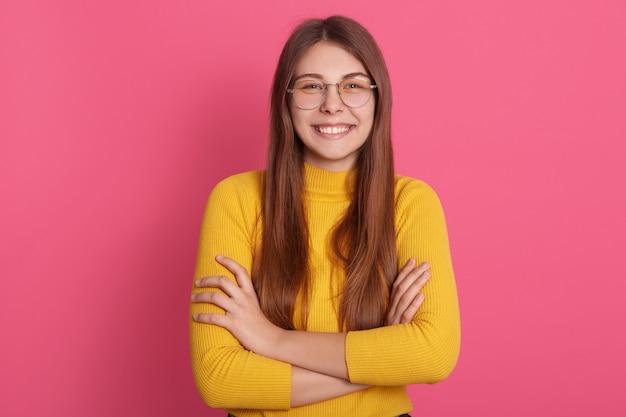 Obraz wesołej, radosnej młodej kobiety, uśmiechającej się szczerze, wyglądającej bezpośrednio po założonych ramionach, z przerwą w zębach