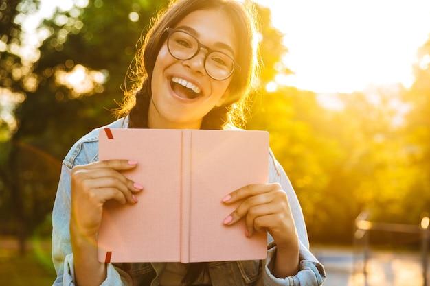 Obraz wesołej ślicznej młodej studentki w okularach, siedzącej na zewnątrz w parku przyrody, trzymając książkę.