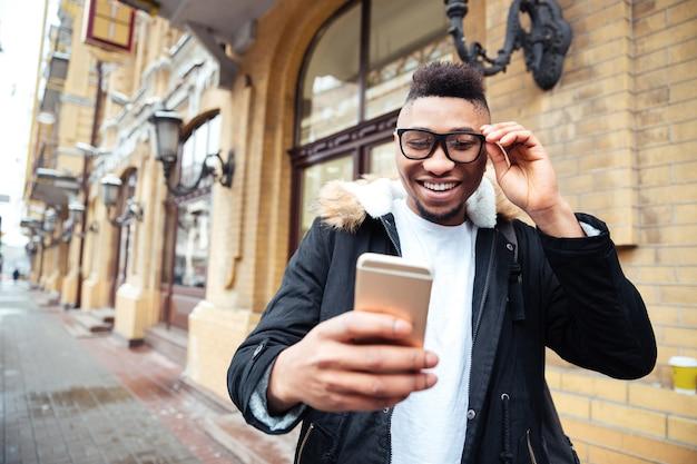 Obraz wesoły mężczyzna trzymając telefon w ręce i zrobić selfie na zewnątrz.