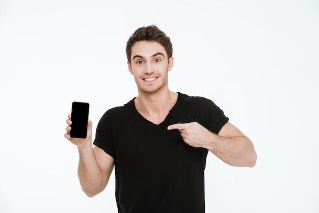 Obraz wesoły młody człowiek ubrany w czarny t-shirt stojący na białym tle pokazujący wyświetlacz telefonu i wskazujący.