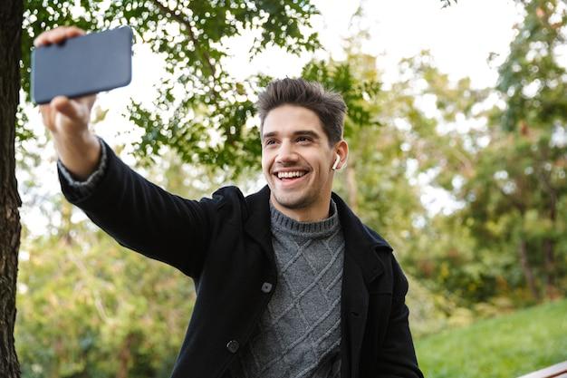Obraz wesoły młody człowiek w odzieży casual spaceru na świeżym powietrzu w zielonym parku przy użyciu telefonu komórkowego weź selfie.