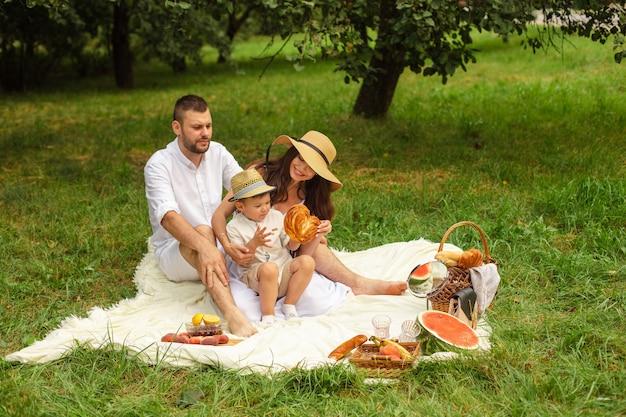 Obraz wesoły młody kaukaski kobieta i mężczyzna trzyma swoje dziecko na rękach, uśmiecha się i raduje