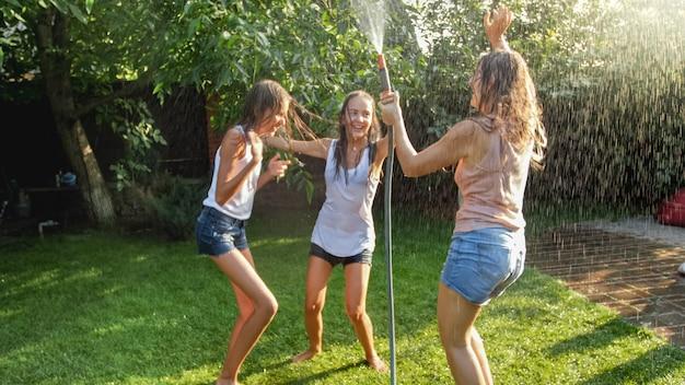 Obraz wesoły roześmiany dziewczyny w mokrych ubraniach tańczących w ogrodzie i trzymający wąż wodny. rodzinna zabawa i zabawa na świeżym powietrzu latem