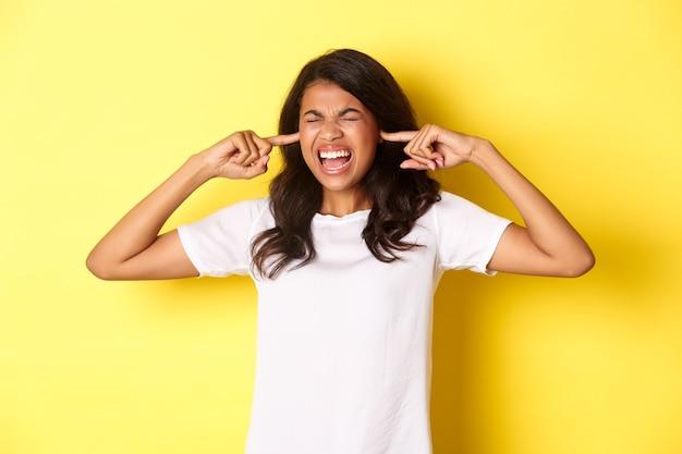 Obraz wkurzonej afroamerykańskiej dziewczyny, która nie może znieść głośnego uciążliwego hałasu, ma zamknięte uszy i krzyczy zirytowany, stojąc na żółtym tle.