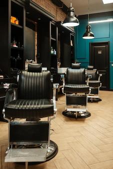 Obraz wnętrza salonu fryzjerskiego z bardzo stylowymi i zabytkowymi krzesłami