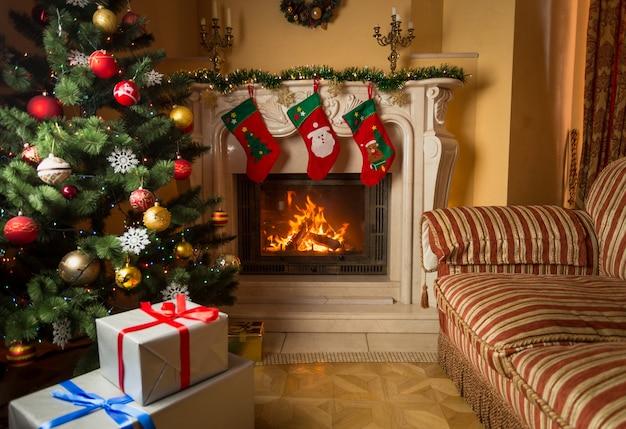 Obraz wnętrza salonu z płonącym kominkiem, ozdobiona choinka