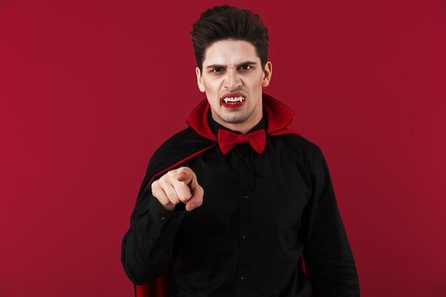 Obraz wściekłego wampira z krwią i kłami w czarnym kostiumie halloweenowym wskazującym palcem z przodu