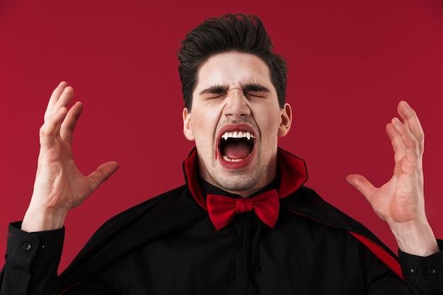 Obraz wściekłego wampira z krwią i kłami w czarnym kostiumie na halloween krzyczy