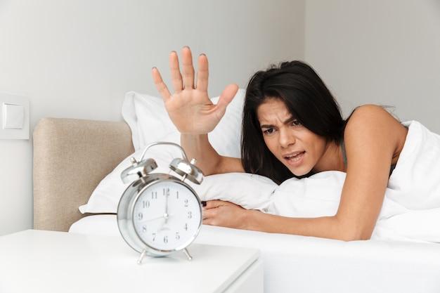 Obraz wściekłej kobiety 20s leżącej w łóżku na poduszce i wyłączającej dzwonienie budzika na szafce nocnej