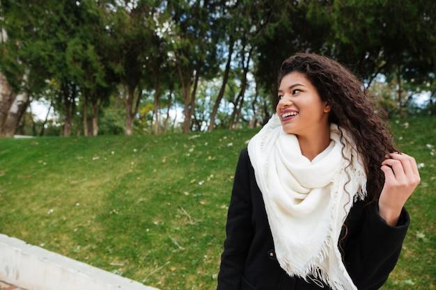 Obraz wspaniałej młodej afrykańskiej kręconej damy noszącej duży biały szalik dotykający jej włosów i patrzącej na bok z uśmiechem na zewnątrz.