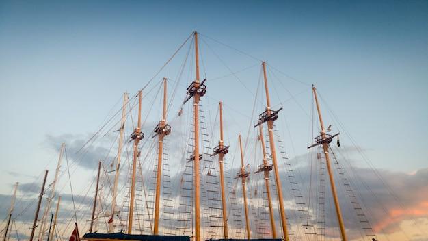 Obraz wysokich drewnianych masztów starych statków w porcie na tle błękitnego nieba wieczorem