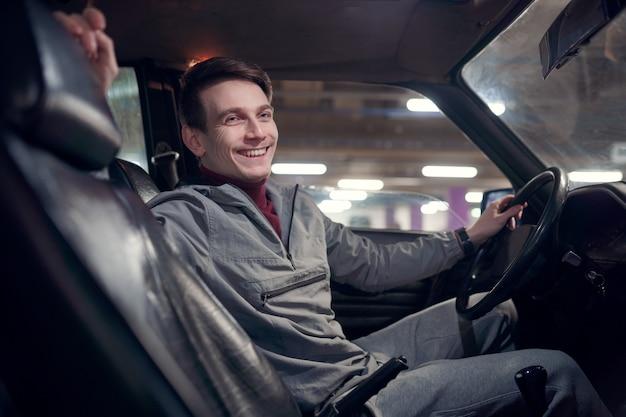 Obraz z boku szczęśliwego mężczyzny patrzącego na kamerę siedzącą w samochodzie