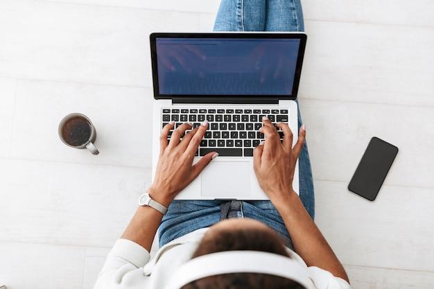 Obraz z góry młoda dziewczyna african american sobie słuchawki za pomocą laptopa, siedząc na podłodze w jasnym salonie