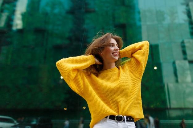 Obraz z piękną, młodą dziewczyną, uśmiechając się i ubierając w żółty sweter