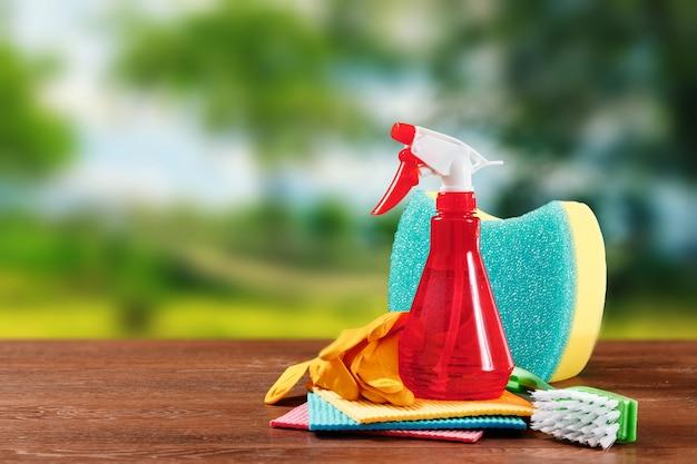 Obraz z różnymi narzędziami do czyszczenia pomieszczeń i środkami czyszczącymi na rozmytym naturalnym tle