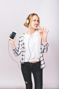 Obraz zachwyconej uroczej wesołej dziewczyny słuchającej muzyki i cieszącej się swoim ekscytującym życiem. radosny i pozytywny nastrój. szczupła sylwetka. zadowolona twarz. jasne emocje.