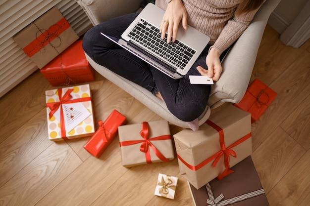 Obraz zadowolona miła kobieta trzyma kartę kredytową z miejsca na kopię za pomocą laptopa
