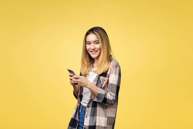 Obraz zadowolonej azjatyckiej kobiety z długimi włosami, uśmiechając się i wysyłając sms-y na telefon komórkowy