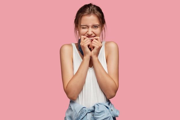 Obraz zadowolonej nastolatki mruga oczami, trzyma ręce przy ustach