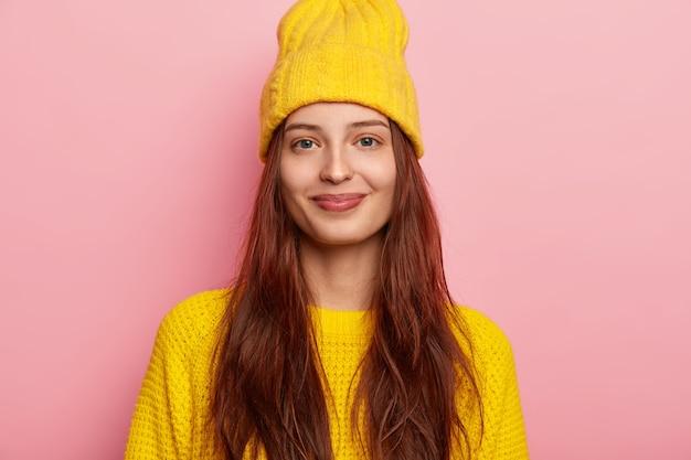 Obraz zadowolonej ślicznej młodej modelki w stylowej żółtej czapce i swetrze z dzianiny, ma długie włosy, pozuje na różowym tle, pokazuje jej zimowy strój patrzy prosto w kamerę z delikatnym uśmiechem