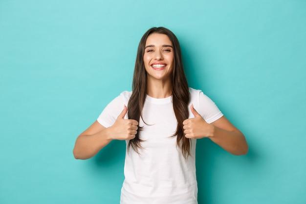 Obraz zadowolonej, uśmiechniętej brunetki, ubranej w białą koszulkę, z uniesionymi kciukami w górę, jakby