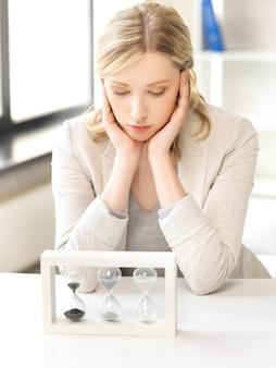 Obraz zamyślonej bizneswoman z piaskowym szkłem