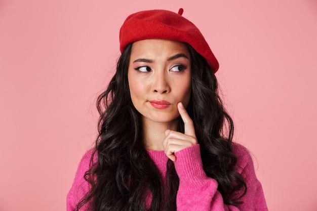 Obraz zamyślonej pięknej azjatyckiej dziewczyny o długich ciemnych włosach, noszącej beret myślący lub wahający się