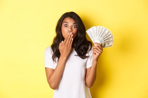Obraz zaskoczonej afrykańskiej dziewczyny wygrywającej pieniądze, dyszącej zdumiony, stojącej na żółtym tle