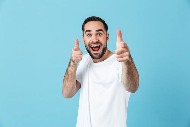 Obraz zaskoczony emocjonalny młody krzyczący szczęśliwy brodaty mężczyzna pozowanie na białym tle nad niebieską ścianą, wskazując do ciebie.