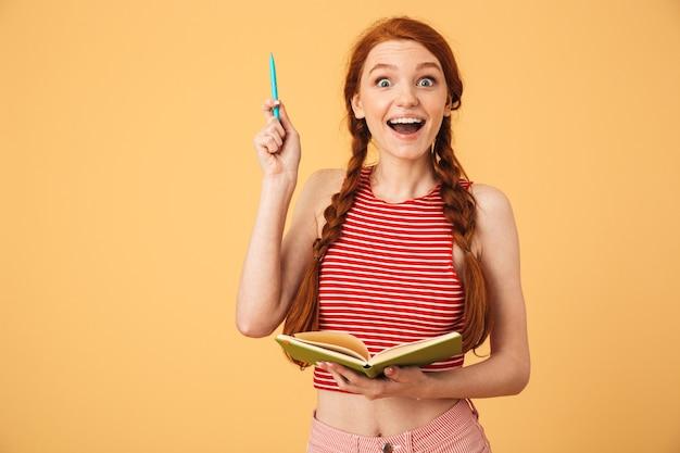 Obraz zaskoczony młoda piękna ruda kobieta pozuje na białym tle nad żółtą ścianą, trzymając czytanie książki, ma pomysł.