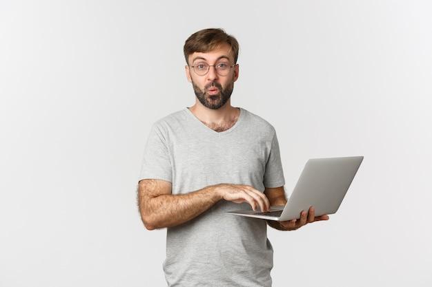 Obraz zaskoczony model męski w okularach i szarej koszulce