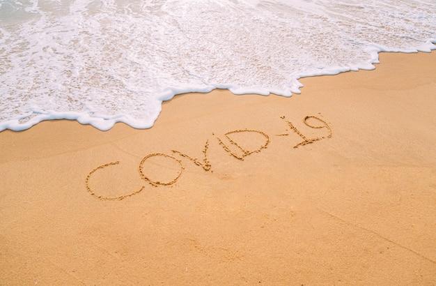 """Obraz zbliżenie fal morskich zmywających słowo """"covid-19"""" z piasku na plaży"""