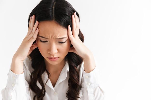 Obraz zdenerwowany lub zmęczony azjatycki biznes kobieta ubrana w odzież biurową siedzi przy stole i chwytając głowę rękami