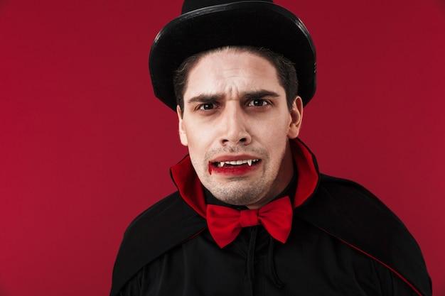 Obraz zdezorientowanego wampira z krwią i kłami w czarnym kostiumie na halloween