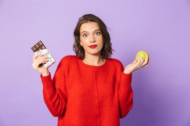 Obraz zdezorientowanej młodej kobiety, pozowanie na białym tle nad fioletową ścianą, trzymając czekoladę i jabłko.
