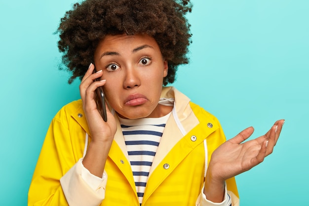 Obraz zdezorientowanej, nieświadomej niezdecydowania, ciemnoskóra kobieta unosi dłoń i dzwoni przez telefon komórkowy