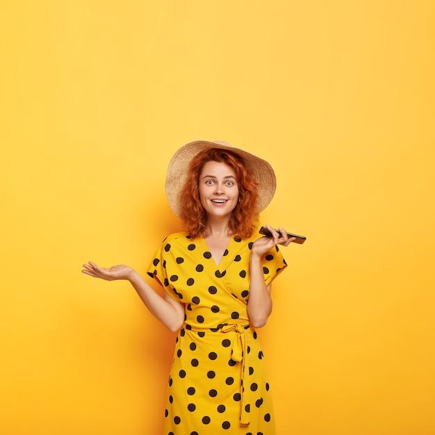 Obraz zdezorientowanej, zaskoczonej, pięknej rudowłosej pani podnosi dłoń, trzyma telefon komórkowy, cieszy się z nowego zakupu, nosi słomkowy kapelusz i żółtą sukienkę w kropki. kobiecość, styl życia