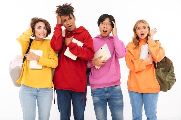 Obraz zdezorientowanej, zszokowanej młodej grupy studentów przyjaciół stojących na białym tle.