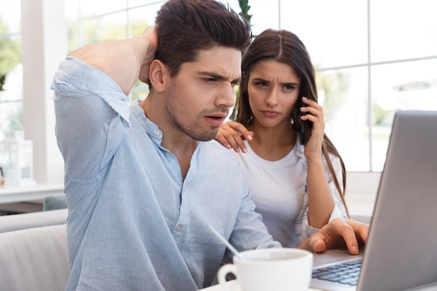 Obraz zdezorientowany niezadowolony młoda para miłości siedzi w kawiarni przy użyciu komputera przenośnego rozmawia przez telefon.