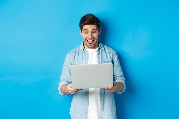 Obraz zdumionego i szczęśliwego mężczyzny reagującego na specjalną ofertę w internecie, patrzącego na podekscytowanego laptopa, stojącego na niebieskim tle.