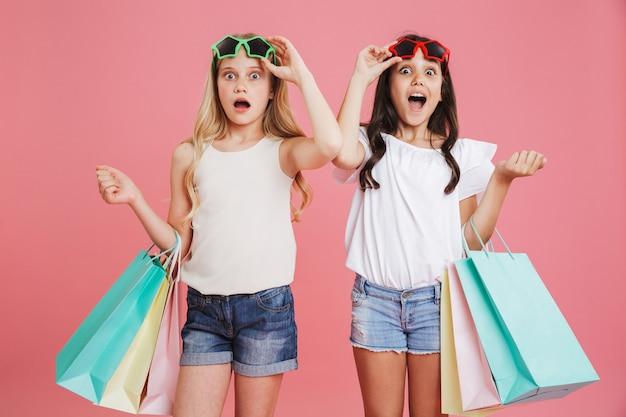 Obraz zdumionej brunetki i blondynki w wieku 8-10 lat w swobodnym ubraniu, patrząc spod okularów przeciwsłonecznych, trzymając kolorowe torby na zakupy z zakupami, odizolowane na różowym tle