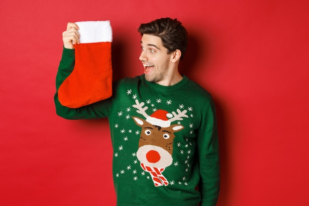 Obraz zdziwionego i rozbawionego mężczyzny w zielonym swetrze, patrzącego na świąteczną skarpetę z prezentami i uśmiechniętego, stojącego na czerwonym tle