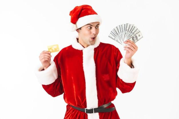 Obraz zdziwiony mężczyzna 30s w stroju świętego mikołaja trzymającego dolary i kartę kredytową