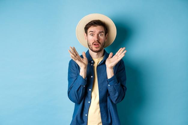 Obraz zszokowanego turysty w panikującym słomkowym kapeluszu, podnoszącym ręce do góry i wpatrującym się w kamerę, stojąc na niebieskim tle.