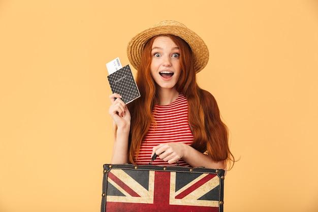 Obraz zszokowanej, podekscytowanej, ślicznej młodej ładnej rudowłosej kobiety pozującej na białym tle nad żółtą ścianą, trzymającej walizkę i paszport z biletami