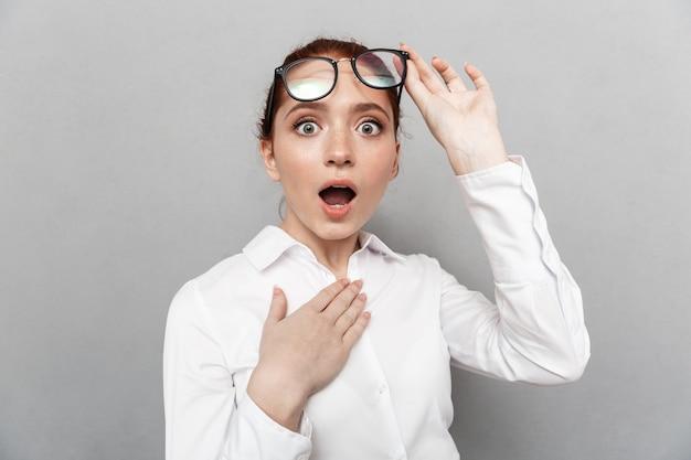 Obraz zszokowanej rudowłosej bizneswoman 20s w okularach, zastanawiającej się w biurze na białym tle nad szarym