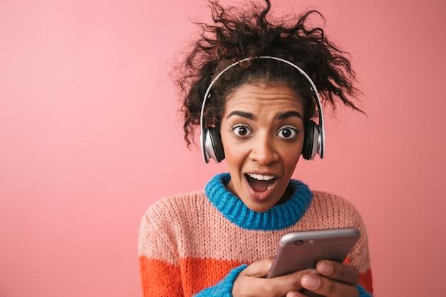 Obraz zszokowany emocjonalny piękna młoda afrykańska kobieta pozowanie na białym tle słuchanie muzyki w słuchawkach za pomocą telefonu komórkowego.